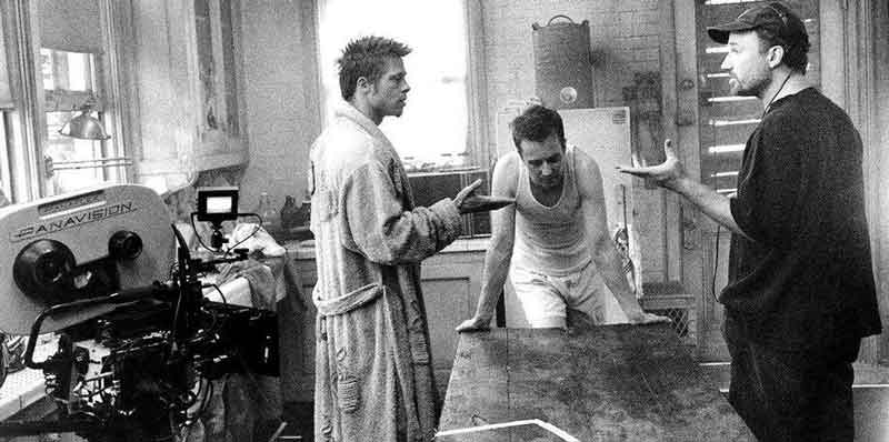 Brad Pitt, Edward Norton, and David Fincher discussing a scene on the set of the ramshackle Paper Street house.