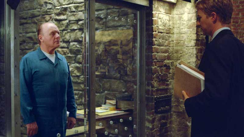 Lecter stares down Graham in a prison scene with a colour palette coming close to matching Scott's later scenes in Hannibal.